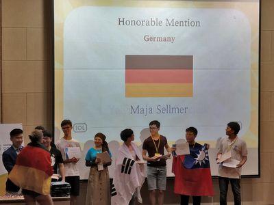 Maja Sellmer auf dem Weg zur Bühne. Auf einer Leinwand ist ihr Name, Land und die deutsche Flagge eingeblendet.