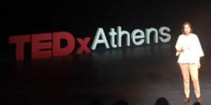 Artemis on stage in front of TEDxAthens logo